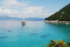 On the edge of green slopes lies the turquoise ocean of Divna Beach